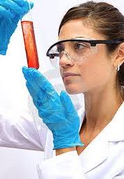 woman in protective eyerwear looking at test tube